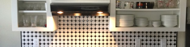 An image of a kitchen featuring dark work surfaces with cream kithcen cabinets and a monochrome tiled wall.