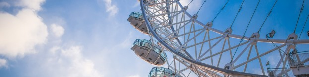 An image of the London eye, taken from the ground on a sunny day.