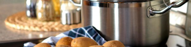 An image of a pile of potates in a kitchen, next to a cooking pot.