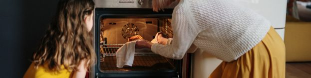 image of mother and daughter cooking together and putting something in the oven